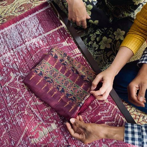 Ikat Fabric weavers with the fabric in the loom and the stunning finished piece