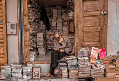 Book Seller sitting in his bookshop engrossed in a book.