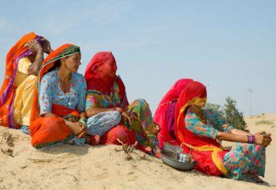 rajasthani woman dressed in bright saris sitting in desert
